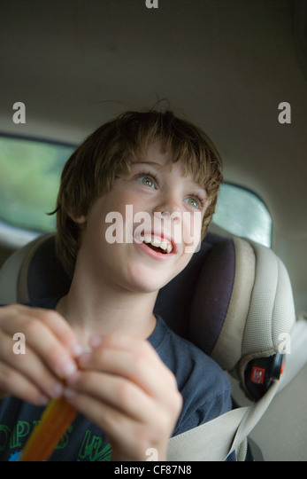 Eight year old boy looking our of car window with expression of wonder and amazement. - Stock Image