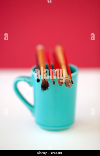 ARtists coffee cup with paint brushes - Stock Image