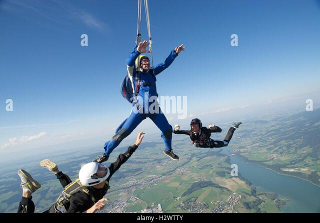 Two instructors assist a student skydiver during the opening of his parachute. - Stock Image