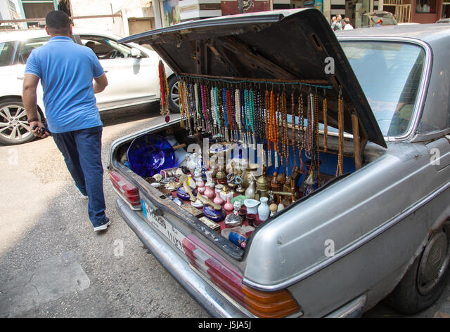 A man selling prayer beads and souvenir from the trunk of his car in the street, Beirut Governorate, Beirut, Lebanon - Stock-Bilder