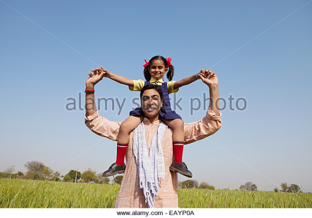 Indian man carrying his daughter on his shoulders - Stock-Bilder