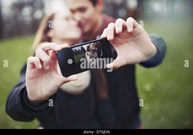 Romantic teenage couple taking self portrait with cell phone at the park. Young man and woman in love. - Stock-Bilder