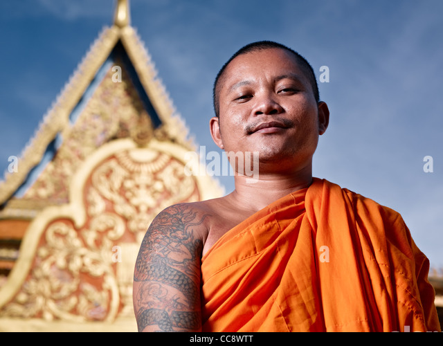 Mid adult Asian monk smiling at camera in buddhist monastery, Phnom Penh, Cambodia, Asia. Low angle - Stock Image