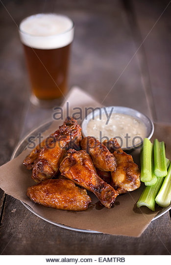 Tray of sauced wings, blue cheese and celery with a pint of beer on a rustic wood surface. - Stock Image