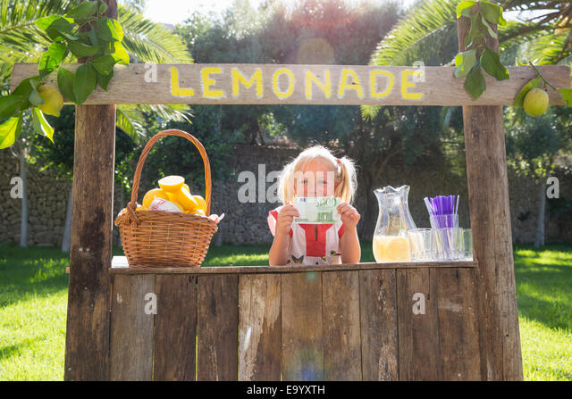 Portrait of girl on lemonade stand holding up one hundred euro note - Stock Image