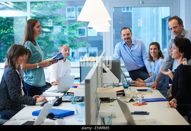 Businesspeople meeting around desk - Stock Image