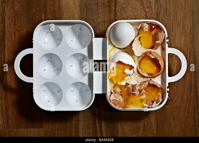 Broken eggs in a carton - Stock Image