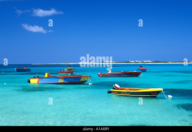 Anguilla caribbean green water yellow red fishing boats blue sky background iconic island symbol ideal perfect paradise - Stock Image