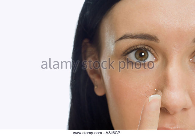 Woman holding contact lens - Stock Image