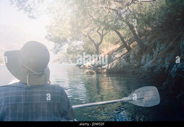 Woman wearing hat canoeing - Stock-Bilder