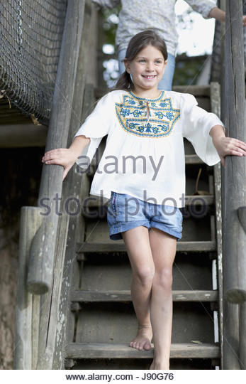 Young Girl Climbing Steps In Adventure Playground - Stock-Bilder