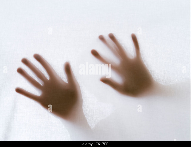 Man's hands behind sheet - Stock Image