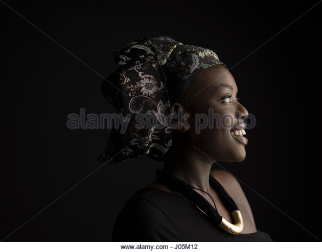 Profile portrait smiling African American woman with headscarf looking away against black background - Stock Image