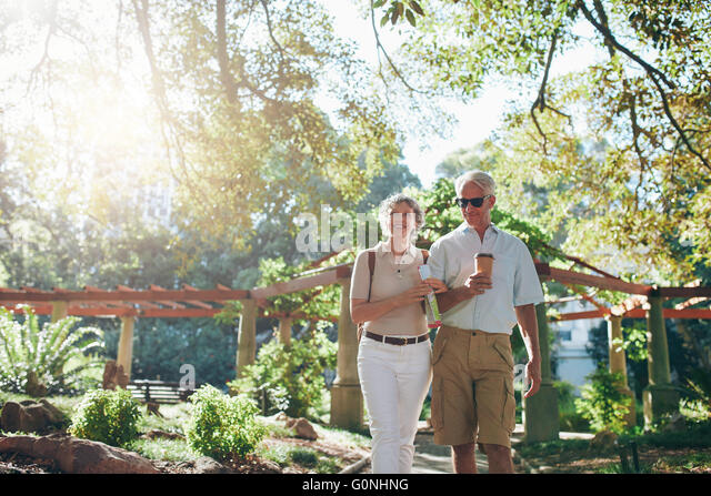 Portrait of couple of senior tourist walking through a park on a summer day. mature couple on a vacation. - Stock-Bilder