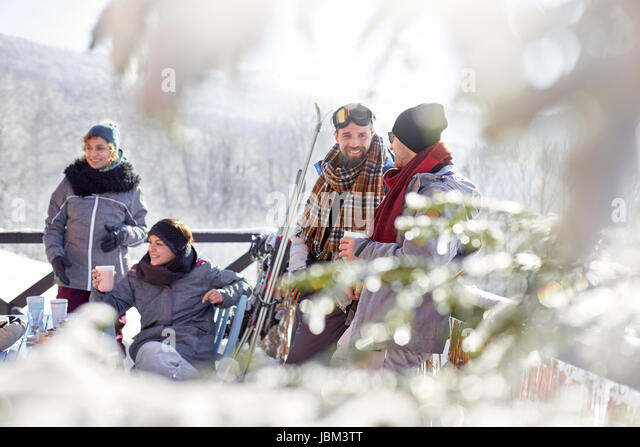 Skier friends relaxing, drinking coffee and hot cocoa apres-ski - Stock-Bilder