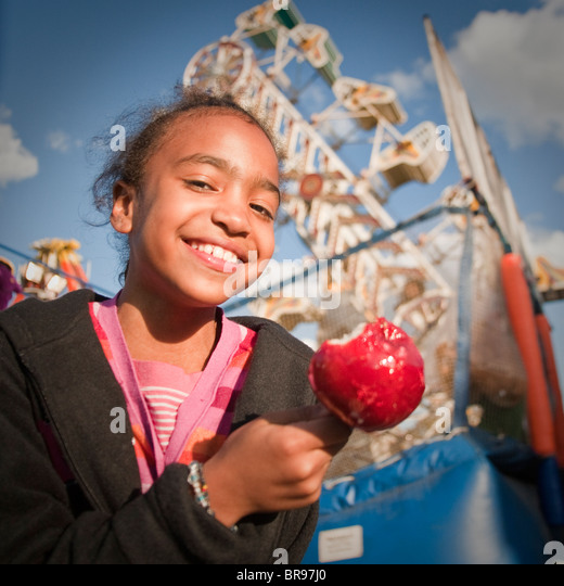 girl eats a candied apple at a state/county fair - Stock Image