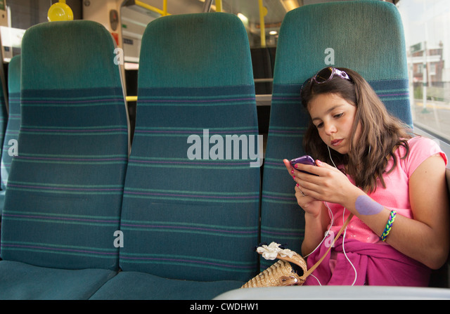 Young girl listens to music on the public transport,London,England - Stock Image