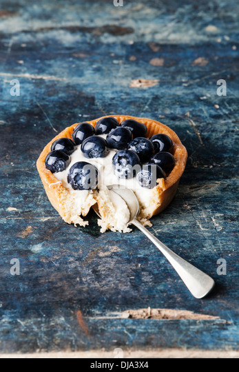 Blueberry tart on blue wooden background - Stock Image