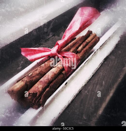 Natural cinnamon wrapped in a red bow sitting on a radiator. - Stock Image