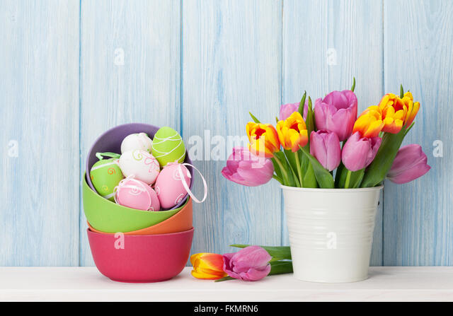 Easter eggs and tulips bouquet on shelf in front of wooden wall View