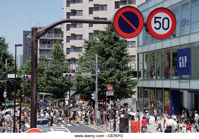 Japan Tokyo Harajuku JR Harajuku Station crowd group crossing street pedestrians traffic signal GAP store traffic - Stock Image