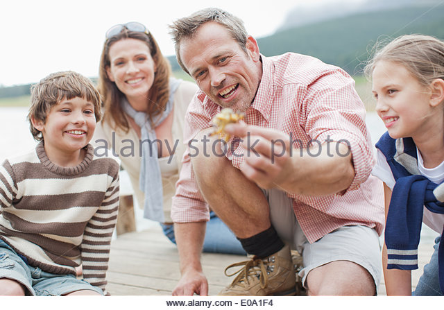 Father holding out small crab - Stock Image