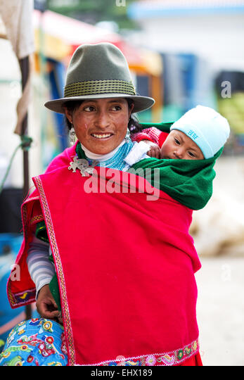 Ecuador, Young native woman with baby wearing red cape and hat - Stock-Bilder