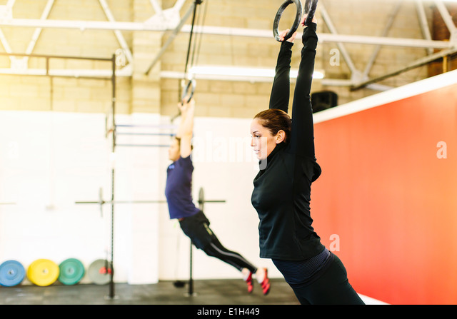 Couple pulling suspended rings in gym - Stock Image