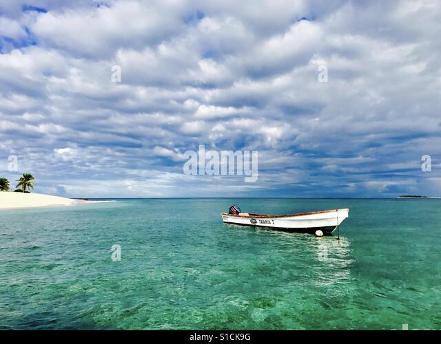 A boat floats off Tavarua island. Tavarua, Fiji. - Stock Image