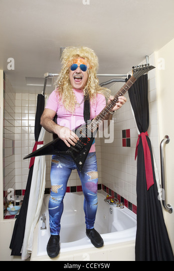Full-length of guitarist playing guitar in bathroom - Stock Image