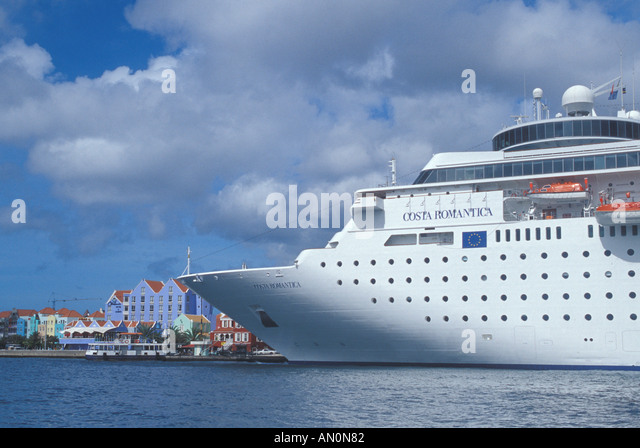 Caribbean islands Curacao Willemstad huge cruise ship dwarfs the city skyline - Stock Image