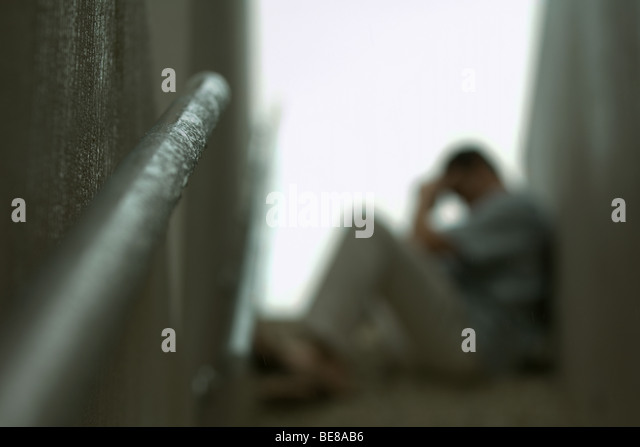 Man sitting on steps of stairwell with head down, defocused - Stock Image