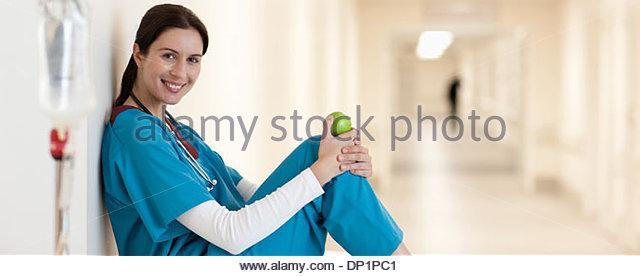 Nurse sitting with apple in hospital corridor - Stock Image