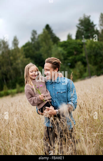 Finland, Uusimaa, Raasepori, Karjaa, Father holding his daughter (6-7) on crop field - Stock Image
