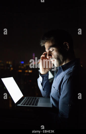 Tired young businessman with laptop in front of skyscraper office window at night, Shanghai, China - Stock-Bilder