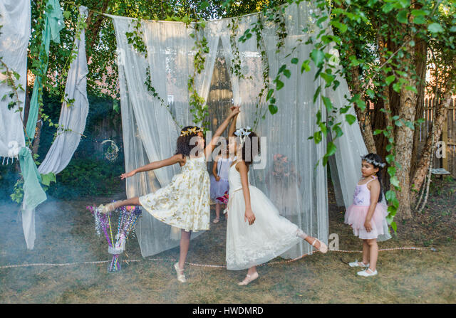 Two young girls, dressed as fairies, dancing outdoors, younger girl watching from side - Stock-Bilder