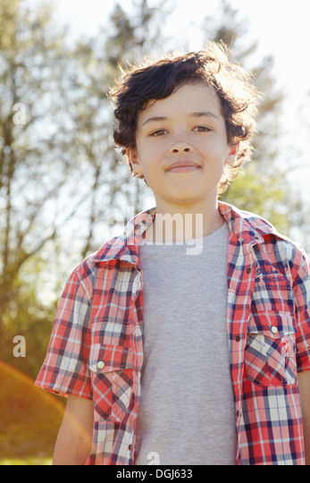 Boy wearing checked shirt in park - Stock Image