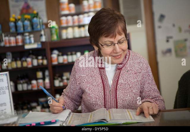 Health foods store owner doing paperwork - Stock Image
