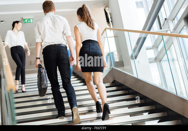 Group of businessman walking and taking stairs in an office building - Stock Image