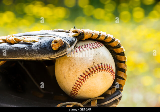 An old worn baseball rests inside an old baseball glove against colorful summer background. - Stock Image