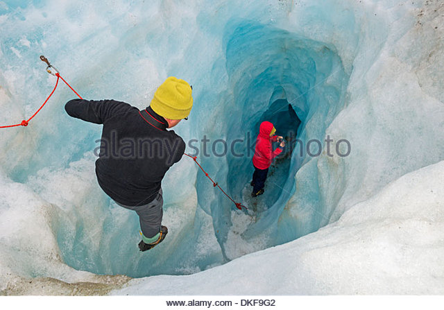 Rock climbers moving down ice cave Fox Glacier, South Island, New Zealand - Stock Image