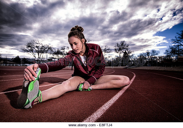 Female runner sitting on running track stretching, Colorado, America, USA - Stock Image