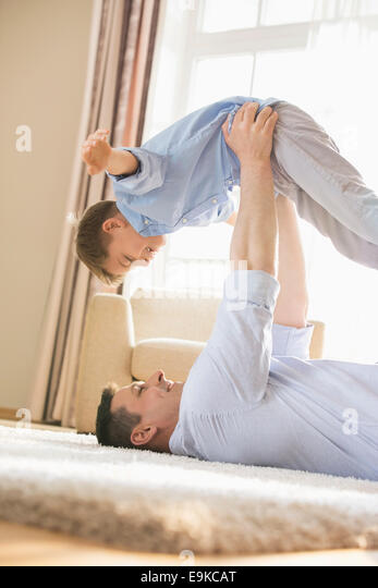 Side view of playful father picking up son while lying on floor at home - Stock Image
