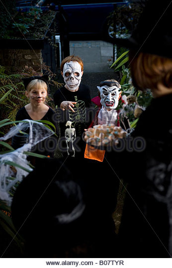 Three friends Trick or Treating at Halloween - Stock Image