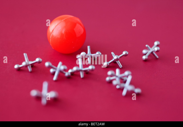Game of jacks and ball on red - Stock Image