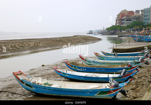 Sampan style fishing boats moored on the shoreline of the Tamsui River estuary at low tide, Tamsui (Danshui), Taiwan - Stock Image