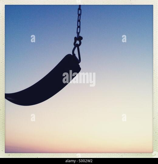 A seat of a children's swing seen with an empty blue sky - Stock Image