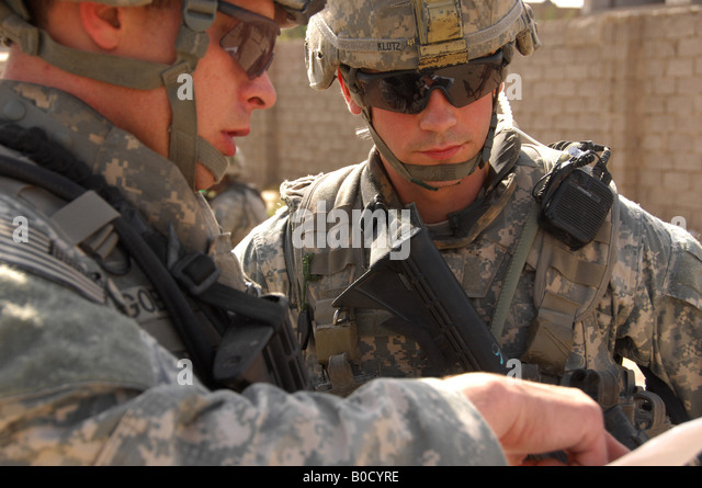 U S Army Staff Sgt Terry Goble left briefs Sgt Robert Klotz prior to a joint patrol through a neighborhood in Shulla - Stock Image
