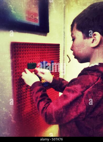 A young boy playing with building blocks in a waiting room. - Stock-Bilder