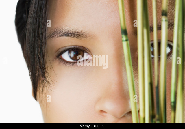 Close-up of a woman's face with plants - Stock Image